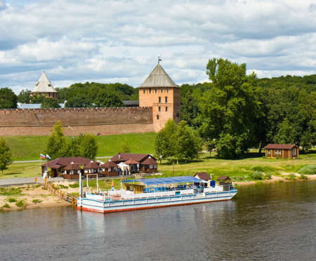 middle ages boat: Middle ages fortress Kremlin on bank of river Volhov and touristic cruise ship in town Great Novgorod, Russia. Editorial