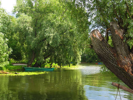 recorded: Summer landscape - little river, willow trees on banks and wooden boat. Recorded in town Pereslavl-Zalesskiy, Russia.