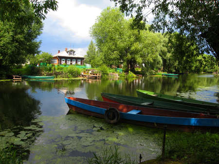 recorded: Landscape - wooden house, little quite river with willow trees on banks, boats. Recorded in town Pereslavl-Zalesskiy, Russia. Stock Photo