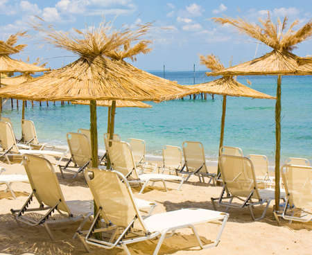helen: Seascape with exotic straw beach umbrellas and chaise longues on sandy beach near sea. Recorded on Saint Constantine and Saint Helen resort, Bulgaria. Stock Photo