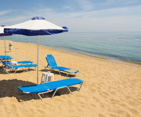 constantine: Beach umbrellas of blue and white colours and blue chaise lounges on sandy beach and sea, recorded on Sants Constantine and Helen resort, Bulgaria. Stock Photo