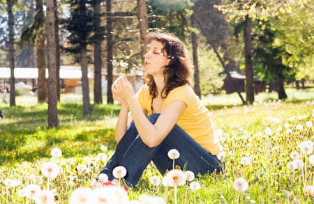 Young European woman with brown hair sit on meadow with white dandelions and blow on flower, fuzzes around.
