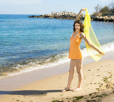 scarf beach: Young European woman with brown hair and orange shirt stands with yellow scarf on sea beach Stock Photo