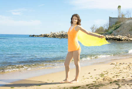scarf beach: Young European woman with brown hair in orange shirt with yellow scarf stands on sea beach. Stock Photo