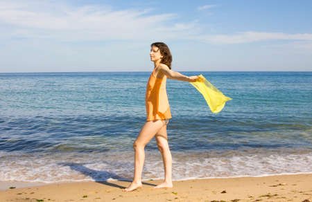 scarf beach: Young European woman with yellow scarf on sea beach.