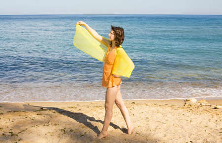 scarf beach: Young European woman with yellow scarf stands on sea beach