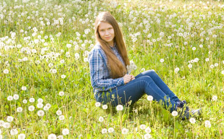 sixteen: Young beautiful girl, sixteen years, European, long brown hair, sits on meadow with white dandelions.