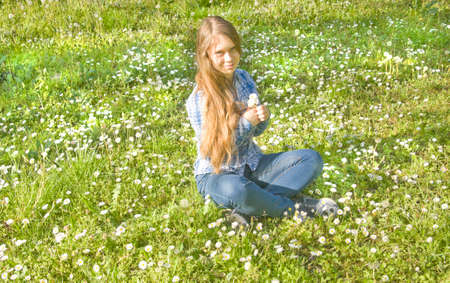 sixteen: Young beautiful girl, European, sixteen years, with long hair, sits on meadow with daisies