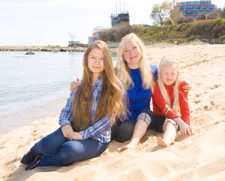 helen: Family - mother with two daughters of different age, sxiteen and nine, sit on beach, recorded in Saint Constantine and Helen resort, Bulgaria.