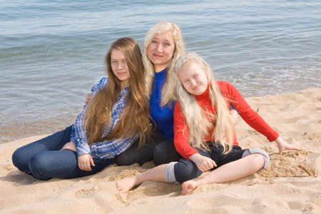nineteen: Mother with two daughters, European, of sixteen and nineteen years, sit on sea beach