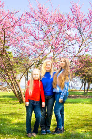 sixteen: Family mother with two daughters, sixteen and nine years, European, in park near pink Cercis tree in blossom.