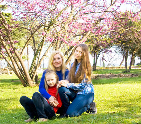 sixteen: Family mother with two daughters - sixteen and nine years, European, sit in park near pink Cercis tree in blossom. Stock Photo