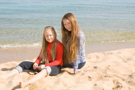 sixteen: Two European sisters, sixteen and nine years, sit on sea beach.