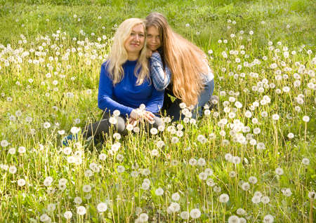 sixteen: Mother and daughter of sixteen years, European, sit on meadow with white dandelions. Stock Photo