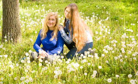 sixteen: European mother and daughter of sixteen years sit on meadow with white dandelions