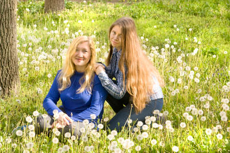 sixteen: European woman with daughter sixteen years sit on meadow with white dandelions.