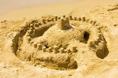 sandcastle: Sandcastle on beach near sea. Stock Photo