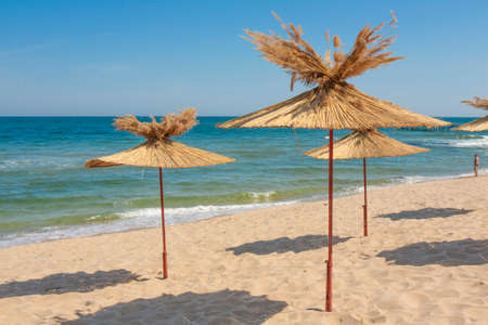 Straw beach umbrellas on sandy beach. Recorded on Saints Constantine and Helena resort, Bulgaria.