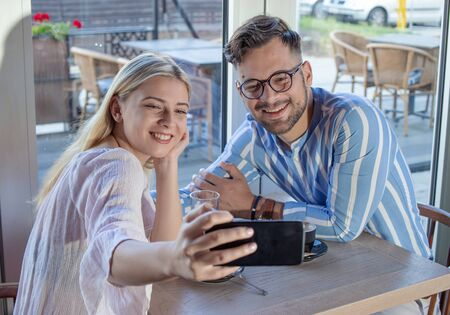 Young romantic couple enjoying a cup of coffee together in a cafe, sitting at the table and taking a selfie with a smartphone.
