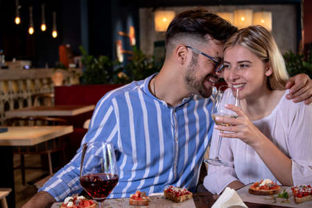 Happy young romantic couple laughing and toasting with wine glasses at dinner in a beautiful fancy restaurant.