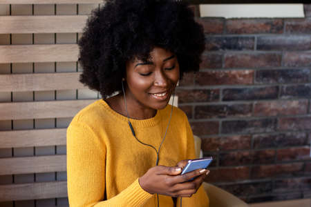 Pensive beautiful female black girl resting in coffee shop listening her favorite music in headphones and chatting in networks. Leisure, technology and urban lifestyle concept.
