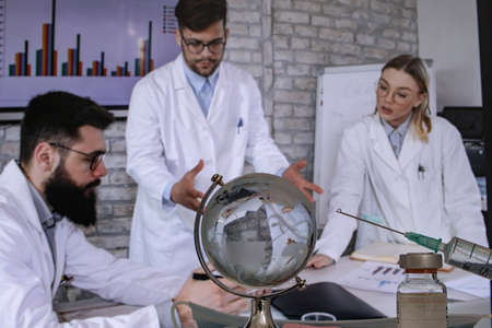 Doctors and medical researchers discussing possible solutions for resolving a global world health crisis by finding a vaccine. Health and medical research concept. Selective focus.