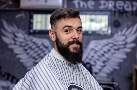 Bearded man posing in a cape after a haircut and beard treatment in front of angel wings graffiti on the wall in a modern barbershop. Barber shop advertising concept. Stock Photo