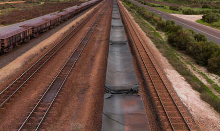 disappears: A long line of railroad trucks, filled with iron ore, disappears to the horizon Stock Photo