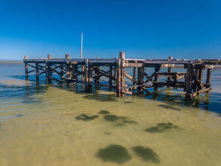 Collapsing old jetty with missing boards stands ready for demolition. Cape Town, South Africa.
