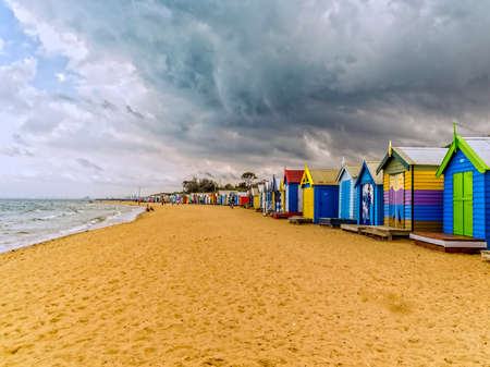 Bathing huts or boxes at Brighton Beach in Melbourne, Rain clouds overhead.Australia, City skyline can be seen in the distance. Foto de archivo