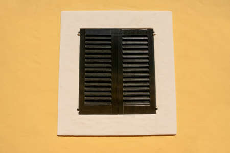 black white window with old shutters in a yellow wall, house facade