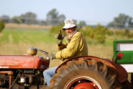 he old: Happy farmer waving from his old red tracktor. Clearly he is very happy being a farmer. Stock Photo