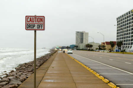 steep cliffs sign: Caution Drop Off sign next to a road warning pedestrians about the drop next to the walkway. This photo was taken on a bleak rainy day in Galveston Texas.