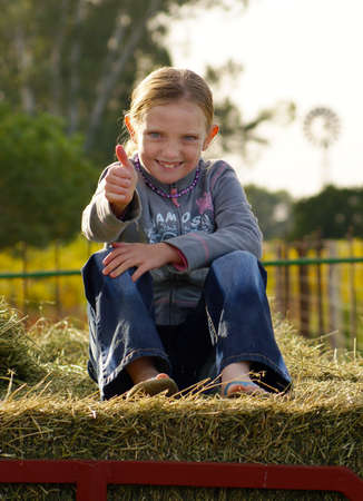 farm girl: Farm Girl sitting on a bale smiling to the camera giving a thumbsup to the camera. Stock Photo