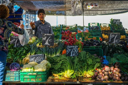 Street market in Madrid, Spain. A storekeeper is attending a woman in a colorful vegetables stand. September, 2017.