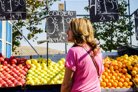 A middle-aged woman in a vegetable stand in a street market in Madrid, Spain.
