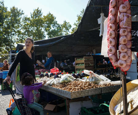 A middle age woman s with her little girl in a walnuts stand in a street market in Madrid, Spain. September, 2017.