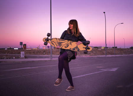 Young redheaded woman with a longboard in an urban place and wintry purple sky. Banco de Imagens