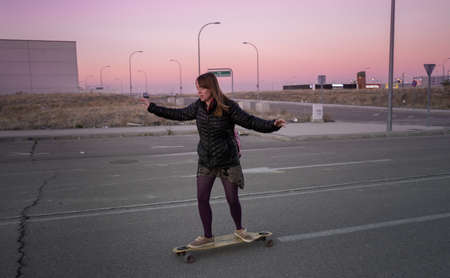 Young redheaded woman riding on the  longboard in an urban place and wintry purple sky.