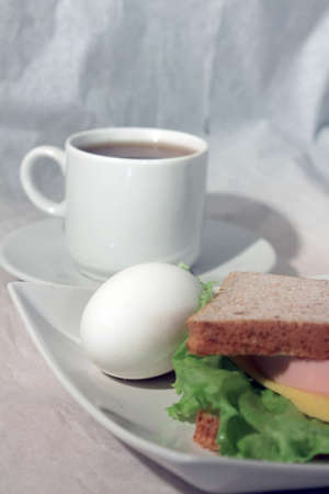 sandwiche: An egg and a sandwiche on a plate and a cup of tea  against light background