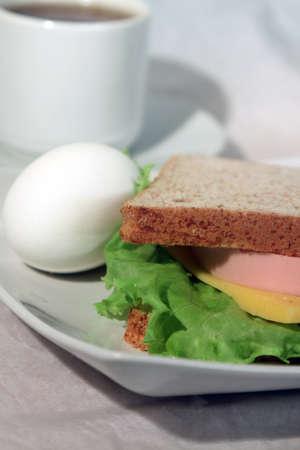 sandwiche: Un uovo e un sandwiche su un piatto e una tazza di t� su sfondo chiaro Archivio Fotografico