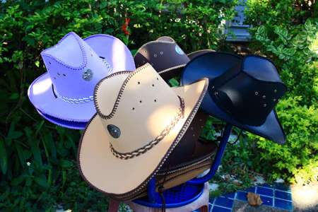variously: Variously Color Cowboy Hat With Seals of the provinces of Thailand Hanging On Leg Chair Stock Photo