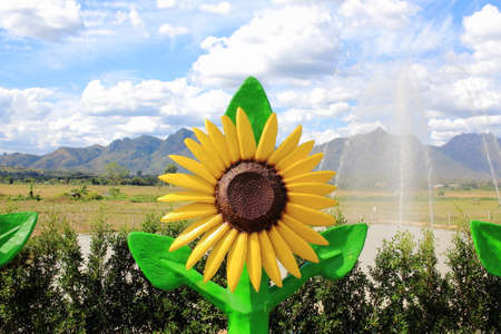 fling: Sunflower Statue Under Blue Sky With Blurry Fountain And Hills Behind the Scene