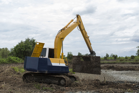 Backhoe Loader working to move soil before construction begin photo