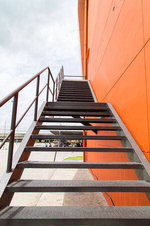 Metal fire escape or emergency exit on Orange Wall of Building with Blue Sky and White cloud photo