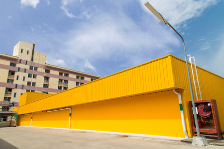 warehouse building: Yellow warehouse Building under Blue Sky and White Cloud