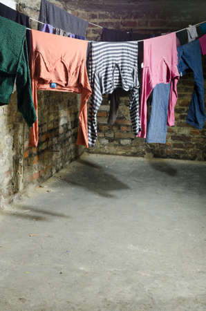 clothes on clothesline in old unhygenig basement photo