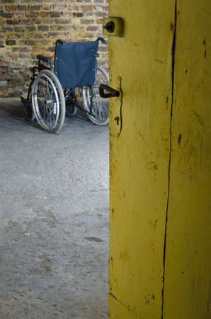 invalidity: empty wheelchair in old basement Stock Photo