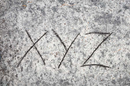 closeup to xyz letters on sand background