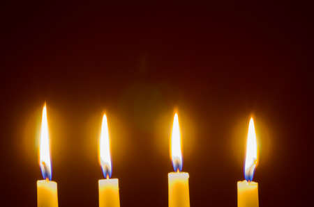 closeup to four candles in dark